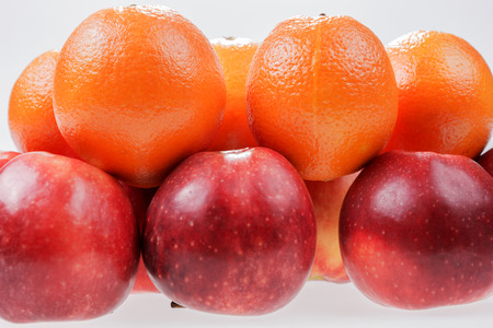 Red apples and oranges on white background 写真素材
