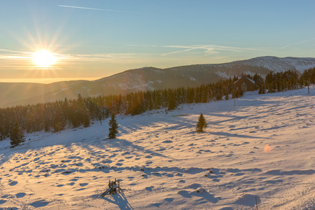 Beautiful winter sunrise with lens flare in Giant mountains, Czech Republic