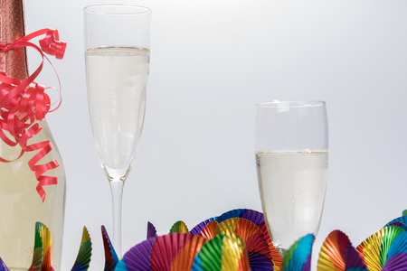 prickling: Two full champagne glasses and champagne bottle with colorful garlands Stock Photo
