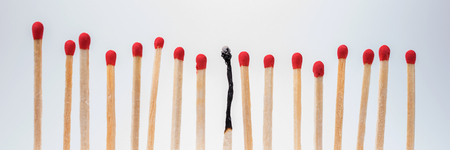 burned out: Burnt match between new matchsticks, shallow depth of field Stock Photo