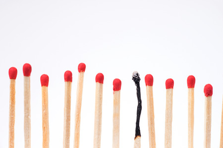 Burnt match between new matchsticks, shallow depth of field Archivio Fotografico