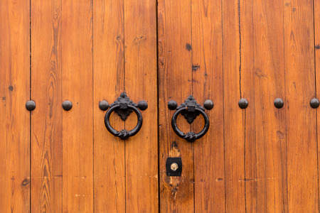 door knob: Ancient closed wooden gate with two door knocker rings Stock Photo
