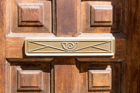 Closeup of letter box in brown wooden door Stock Photo