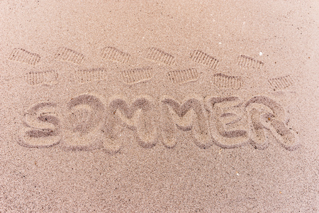 Word summer (Sommer) in german written on the beach