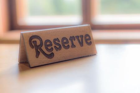 ウィンドウの前にテーブルの上の木製のリザーブ看板 写真素材