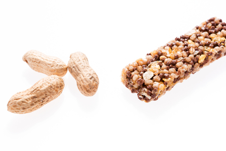 Two healthy granola bar (muesli or cereal bar) and peanuts isolated on white