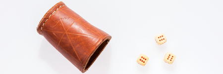 Three dice with leather cup on white background