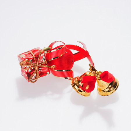 Pair of golden bells with red christmas gift box