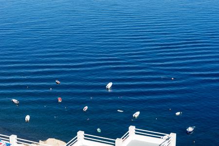 Small boats in the Mediterranean sea off the island of Santorini Stock Photo