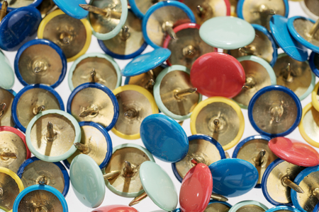 Many different colored thumbtacks, colorful background or texture