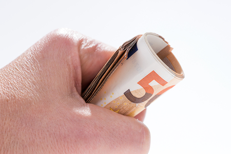 A roll of fifty euro banknotes in the hand