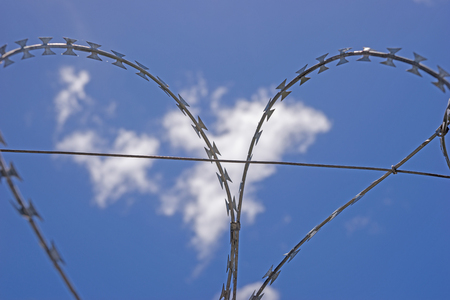 Safety fence of barbed wire against the blue sky with clouds Stock Photo