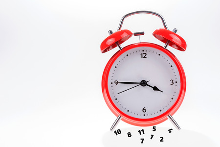 Old retro red alarm clock with falling numbers Stock Photo
