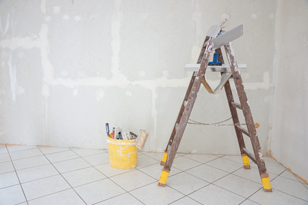 Wooden stepladder and bucket in the room to renovate
