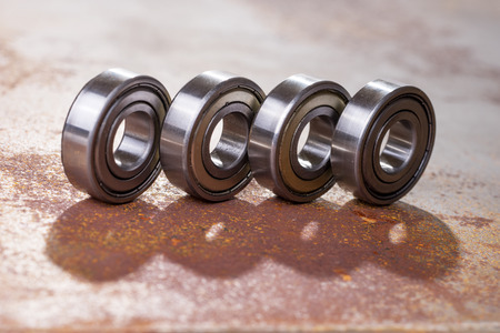 Four metal bearings on rusty surface