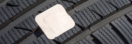Damaged car tire with first aid plaster. First aid concept