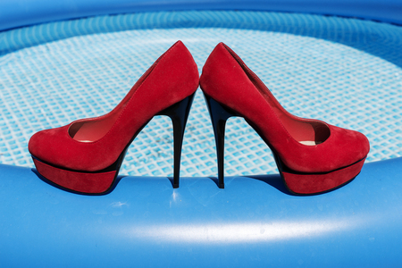 Beautiful red high heels on the edge of the swimming pool Stock Photo