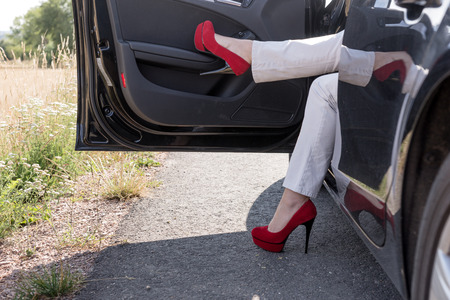Woman gets out of the car. Legs with sexy red high heel shoes