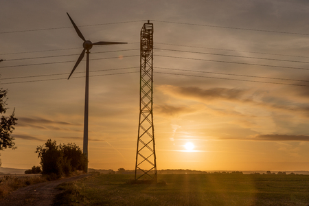 Wind turbine and electricity power line in sunrise. Sustainable development environment friendly concept Banque d'images