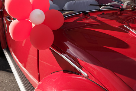 Red wedding car with red and white balloons