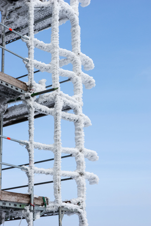 Metal scaffolding with snow and ice on the facade of the house Banque d'images