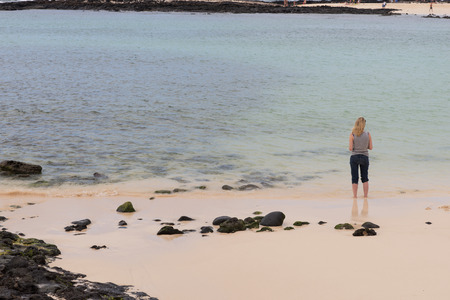 Young woman is standing on the beach at Fuerteventura in the water. View from a back