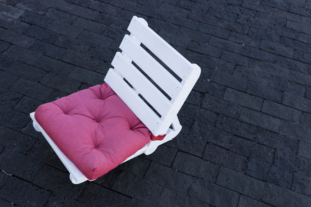 Small white wooden chair on the walkway in the city
