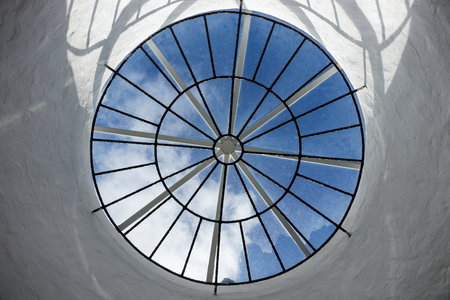 Round roof window with a view of the sky and clouds Stock Photo