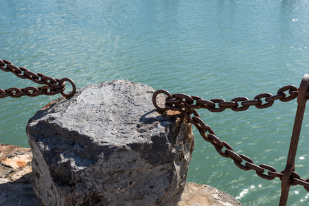 Fence with metal chains. Barrier to the water