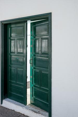 Green wooden open door. Entrance door opened a crack
