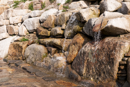 Texture of natural stone and flowing water. The source of water in the mountains