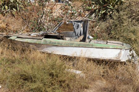 Old abandoned small wooden boat in grass