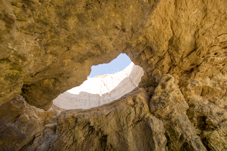 Hole in the rock on the beach. Algarve. Portugal