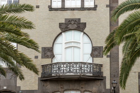 Classical style balcony on the building with palm trees Stock Photo