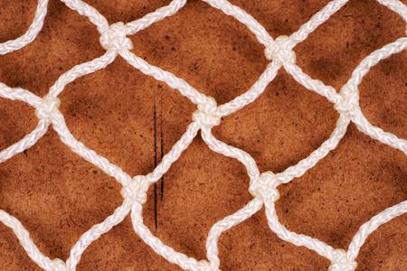 White fishing net over brown background. Fishing net texture