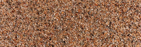 The pattern small brown pebbles stone as background. Panoramic picture
