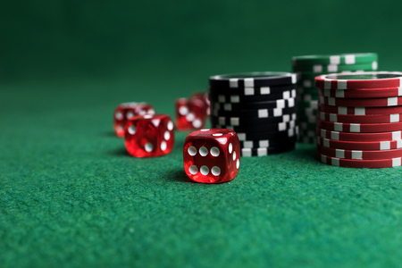 Casino game. Poker chips and red dice on green table