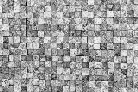 Uneven wall of small gray square stones. Gray wall background