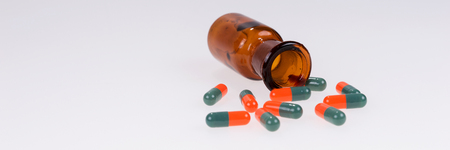 Colorful medical pills pours out of the glass