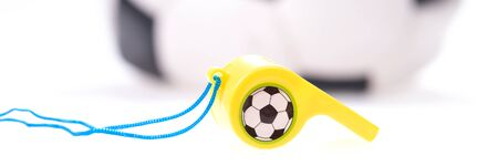 Plastic whistle with cord and soccer ball in the background. Panoramic picture