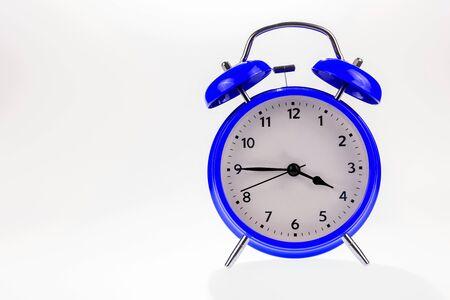 Despertador retro azul aislado en blanco, concepto de tiempo