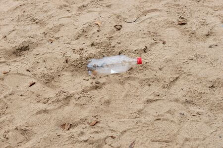 Discarded plastic water bottle in the sand on a beach 写真素材