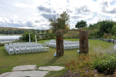 Place for wedding ceremony at the Lakeshore. Wedding arch decorated with flowers and white chairs on each side of archway outdoors 스톡 콘텐츠