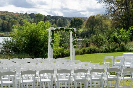 Place for wedding ceremony outdoor. Wedding arch decorated with flowers and white chairs