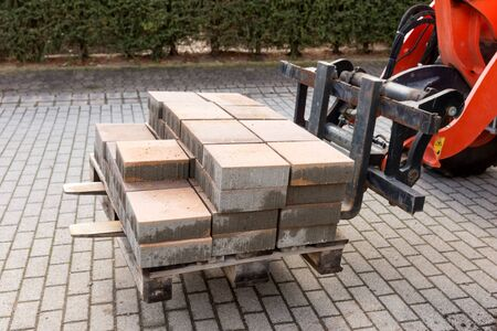Forklift with new paving stones on the wooden pallet