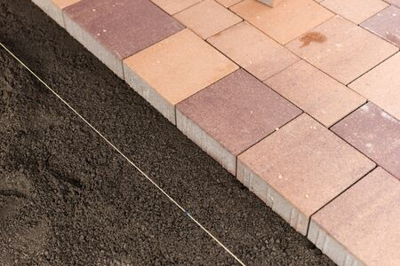 New colorful paving stones along a directional cordon on a prepared flat surface