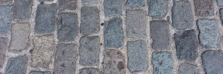 Panoramic background of old cobblestone pavement. Close Up