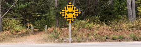 Yellow double arrow traffic sign at the end of a road with a forest. canada
