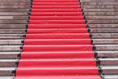 Red carpet over gray concrete stairs. Perspective ascending