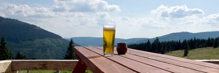 Glass beer on the table in the outdoor restaurant, mountains in the background 版權商用圖片 - 137728226